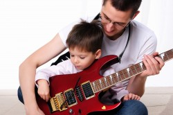 Boy with autism learning guitar with father