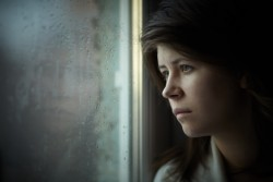 Woman with depression looking out window